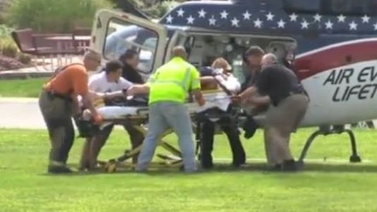 Injured firefighters are loaded into a helicopter.