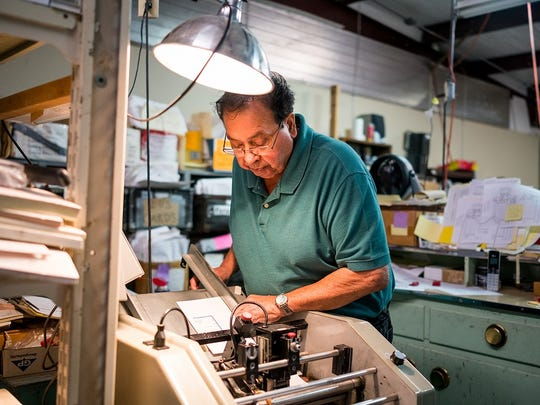 "Deming City Councilman and J and J Printing owner Joe ""Butter"" Milo measures and cuts card stock for customers on Oct. 2, 2017. Milo's parents were first-generation immigrants from Mexico."