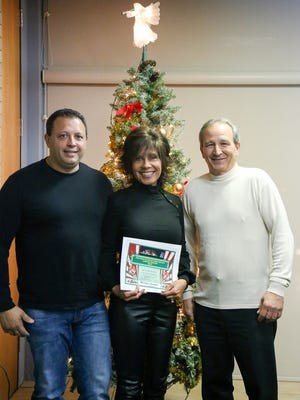 Vineland Municipal Utilities Director John Lillie (right) presents a certificate of achievement and a check for $500 to Ray and Alisa Morales for their holiday display at 1786 Cherokee Lane in Vineland, which captured first place in Vineland's 2017 David Di Giovacchino Holiday Lighting Contest.