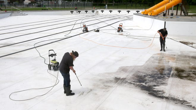 A crew from Hastings Water Works power washes the Dogwood Pool in North Canton, which will reopen July 1, on Wedesday, May 27, 2020. In the foreground is Matt Cox.