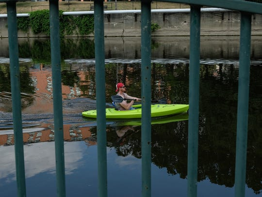 A man floats in his kayak by the Lansing Center Sunday,