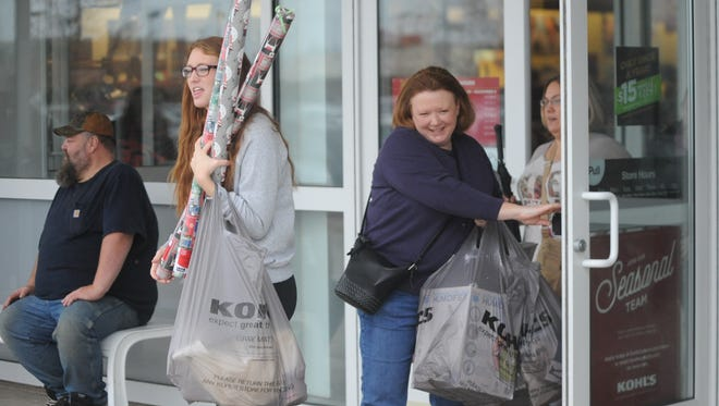 Black Friday shoppers leave Kohl's with their purchases Friday.