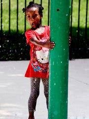 Dakota Scott, 4, stays cool on the Splash Pad at Watkins