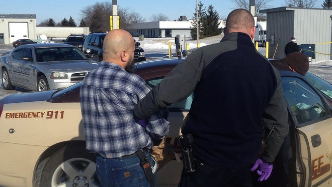 The suspect in a fatal stabbing Tuesday afternoon in Daleville (in blue plaid) waits to be placed in a Delaware County Sherrif's vehicle.