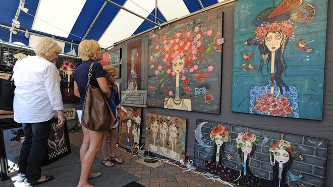 Shoppers peruse the work of  Paula Hallman  during a Red River Revel Arts Festival in downtown Shreveport.