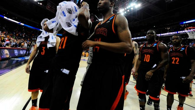 Mercer players Langston Hall (21), Jibri Bryan (34) and Kevin Canevari (3) walk off the court after losing to Tennessee in Raleigh, N.C.