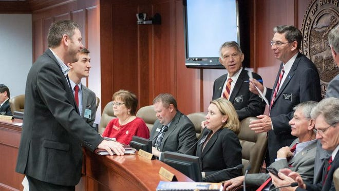 South Dakota budget commissioner Jason Dilges (left) jokes with members of the Legislature's Joint Appropriations Committee during a break in a budget hearing in 2014. Dilges left the job after being placed on indefinite administrative leave. No reason was given for his departure.