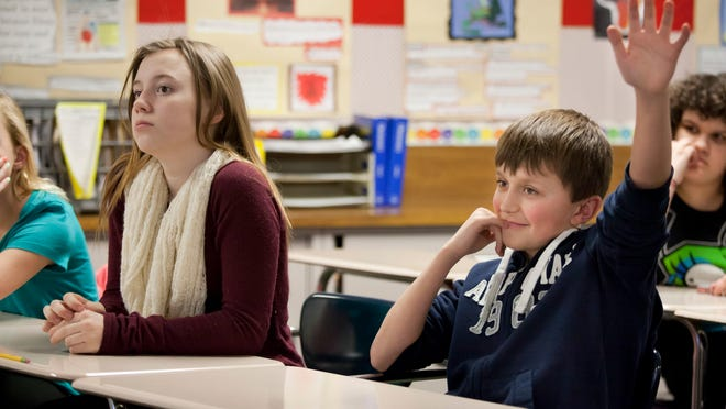 Charlie Bartolomucci, 11, raises his hand next to Aubrey Prater, 11 as they discuss changing campuses with high school students Wednesday, March 4, 2015 at Algonquin Middle School in Algonac. Algonac High School will be converted to a seventh through 12th grade campus as part of a district-wide consolidation.