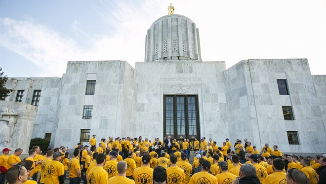 About 300 firefighters from across the state listen as Karl Koenig, legislative director for the Oregon State Fire Fighters Council, addresses them from the steps of the Capitol on Feb. 13.