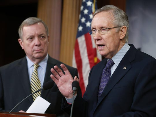 Senate Majority Leader Harry Reid (D-NV) (right) speaks while U.S. Sen. Dick Durbin (D-IL) listens during a news conference on Capitol Hill, on December 12, 2013.