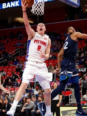 Pistons forward Henry Ellenson (8) goes up for a shot against Timberwolves center Karl-Anthony Towns (32) during the fourth quarter of the Pistons' 122-101 win over the Timberwolves on Wednesday, Oct. 25,2017, at Little Caesars Arena.