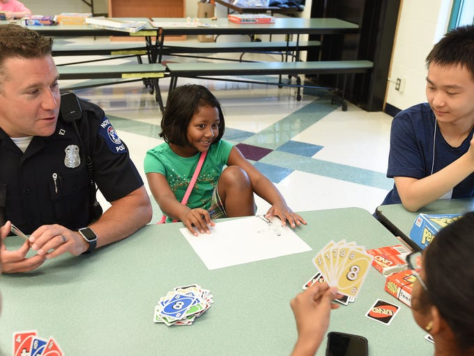 Novi Police Officer Jason Meier plays Uno with Nithya