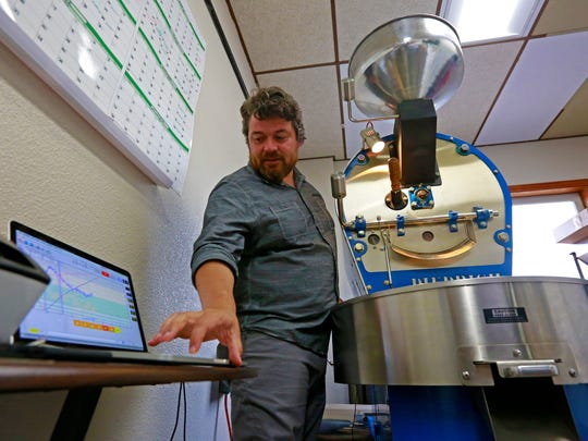 Francisco Guerrero checks for temperature shows on his computer during roasting coffee Monday, June 11, 2018, at Redwood St. Roasters in Edgar, Wis. T'xer Zhon Kha/USA TODAY NETWORK-Wisconsin