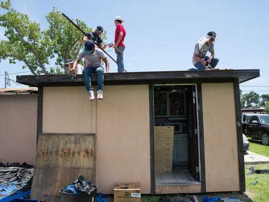 Volunteers with the Bounce recovery project help replace a roof damaged by Hurricane Harvey on a home in Rockport on Wednesday, July 18, 2018.