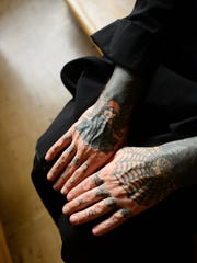 Brother Andre Love, a Benedictine monk, sits in the church after praying at the Mount Angel Abbey. Love, a former tattoo artist, still has tattoos on his hands, arms and neck.