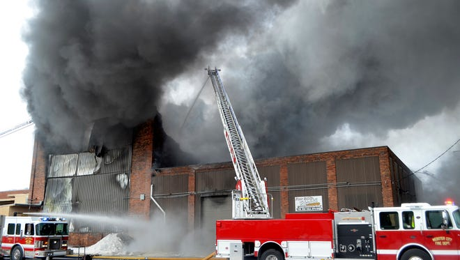 A Webster City ladder truck joins Fort Dodge fire trucks in battling a warehouse fire at the corner of Central Avenue and 15th Street. Two blocks to the east were evacuated due to toxic smoke coming from burning tires and insulation inside the building.