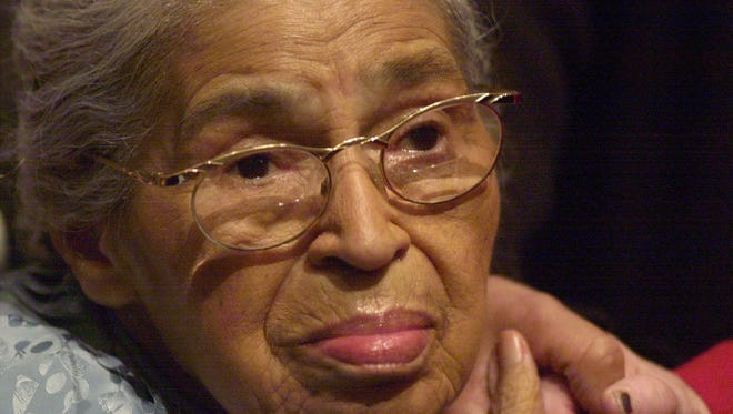 In this Dec. 1, 2001, file photo, civil rights pioneer Rosa Parks holds the hand of a well-wisher at a ceremony honoring the 46th anniversary of her arrest for civil disobedience, at the Henry Ford Museum in Dearborn, Mich. Parks' archive of letters, writings, personal notes and photographs has been fully digitized by the Library of Congress and is now available online. The library announced Wednesday, Feb. 24, 2016, that the collection of about 10,000 items belonging to Parks is available to the public. (AP Photo/Paul Warner, File)