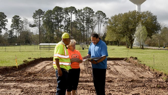 Yvonne Normand, Rod Sias and Doris Barrow look over construction plans for volleyball courts in South City Park.