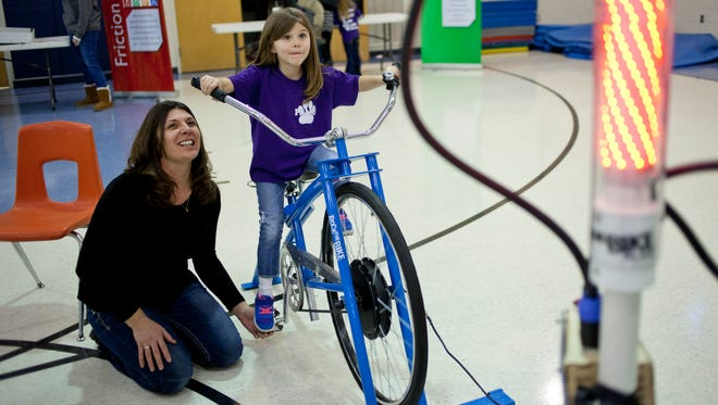 Kindergartner Megan Wormsbacher, 5, concentrates as she pedals a bike to power LED lights with the help of parent volunteer Kelly Ickes during a STEM assembly Friday at Palms Elementary School in Ira Township.