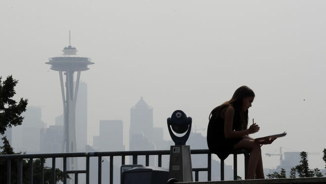 A girl works on a drawing next to an unused viewing scope as a smoky haze obscures the Space Needle and downtown Seattle behind. Tens of millions of people in the Western US face a growing health risk due to wildfires as more intense and frequent blazes churn out greater volumes of lung-damaging smoke, according to research scientists at NASA and several major universities.