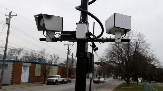 FILE - This file photo made Wednesday, Jan. 16, 2013, in Elmwood Place, Ohio, shows a pair of traffic cameras aimed on Vine Street. The cameras have since been removed by order of a judge. After a string of rulings against traffic cameras, cities that use them are urging the Ohio Supreme Court to uphold the automated speeding and red-light enforcement. (AP Photo/Al Behrman, file)
