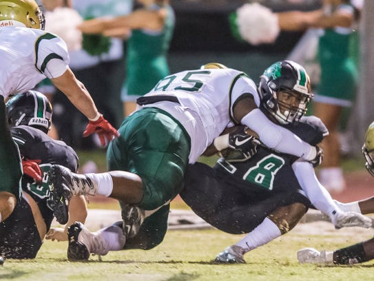 Acadiana High defensive tackle Elisha Sion makes one of his 14 tackles behind the line this season against arch-rival Lafayette High.