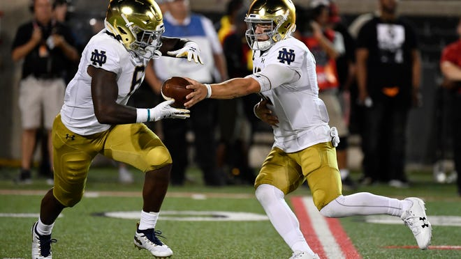 Notre Dame quarterback Ian Book (12) hands the ball off to running back Tony Jones Jr. (6) during the first half of an NCAA college football game in Louisville, Ky., Monday, Sept. 2, 2019. (AP Photo/Timothy D. Easley)