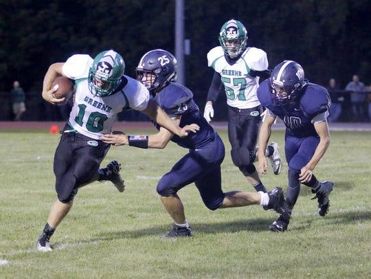 Greene quarterback Coy Austin breaks a tackle on his