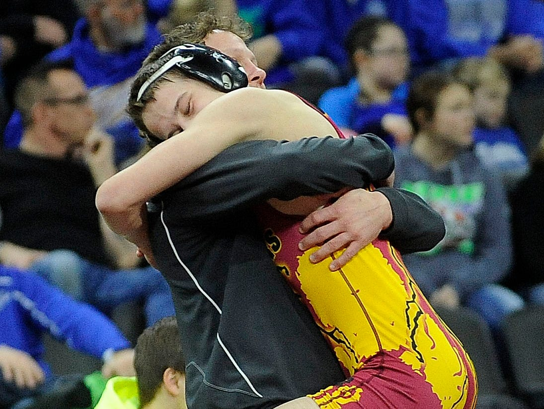 Roosevelt's Brandon Carroll and a coach celebrate a win over Pierre's Michael Lusk for the 113-pound championship last year in Sioux Falls.