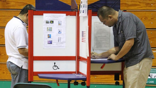 In this file photo, residents vote at the University of Guam Calvo Field House during the November 2014 General Election.