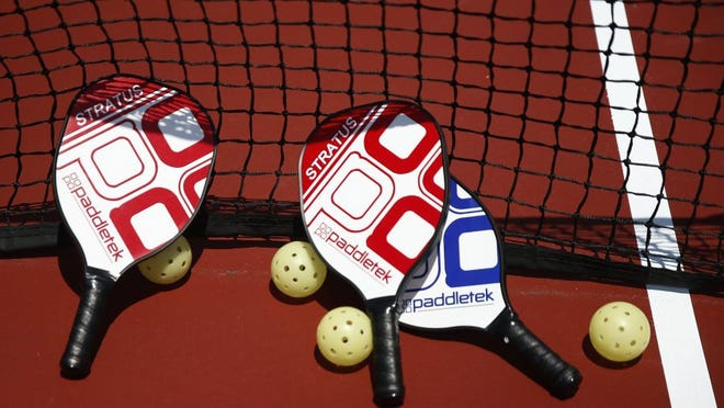 Paddles and balls are organized against the net Tuesday, April 26, 2016 at East Naples Community Park. About 75 local school children came out to enjoy pickleball on Kids' Day as part of U.S. Open Pickleball Championship festivities. Professionals played exhibition matches too. (Corey Perrine/Staff)