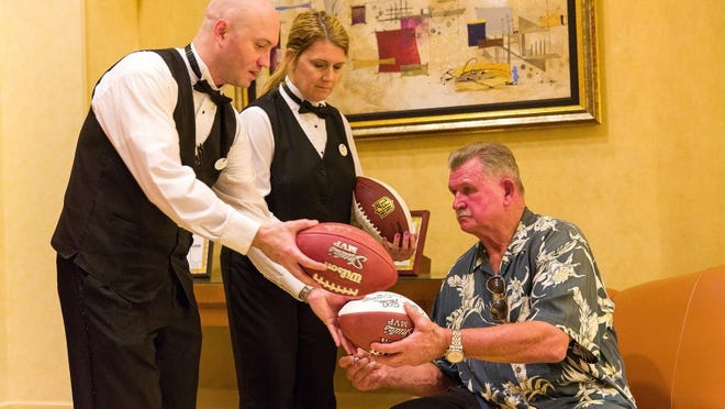 Football Hall of Famer Mike Ditka autographs footballs at a dinner to feature his new wines at Shula's Steak House at the Hilton Naples on Wednesday, March 20, 2013, in Naples.