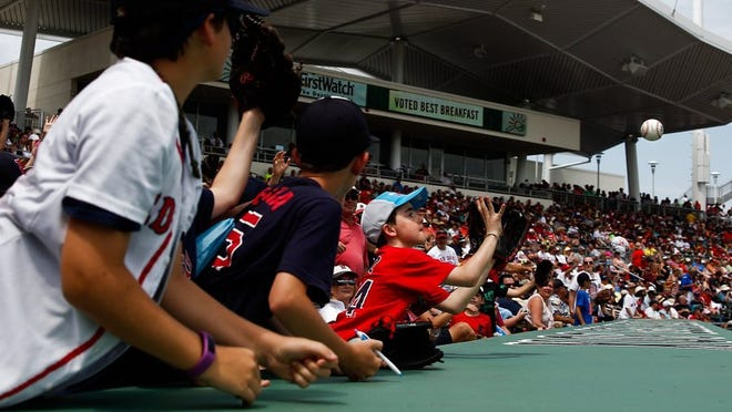Red Sox fans catch a ball from one of the Red Sox during their game against the Orioles at Jet Blue Park on Monday, March 28, 2016. (Scott McIntyre/Staff)