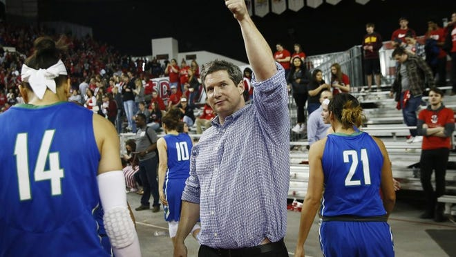 Florida Gulf Coast head coach Karl Smesko gives a thumbs up, flanked by Florida Gulf Coast guard Whitney Knight (14) and Florida Gulf Coast guard Jaime Gluesing (21) to the few fans who made the trip after the loss of the WNIT final Saturday, April 2, 2016 at the DakotaDome in Vermillion, S.D. South Dakota won 71-65. (Corey Perrine/Staff)