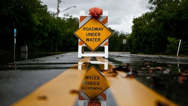 Signs warning high waters were placed on Goodland Dr. in Goodland on Sunday, August 30, 2015.