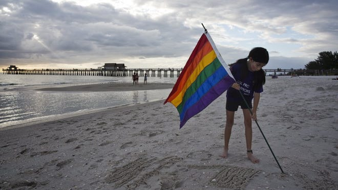 Morgan Tocco, 10, of Naples, draws the LGBT flag in the sand at a seaside vigil for the victims of the Pulse nightclub shooting in Orlando on June 21, 2016. Morgan hoped her drawing would attract some people from the beach to participate in the event.