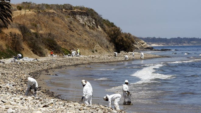STAR FILE PHOTO Crews packed clumps of oil into plastic bags as part of the cleanup of a spill near Refugio State Beach in May 2015.