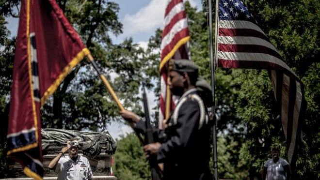 Richard Anderson (left) salutes during the presentation of colors at the annual Memorial Day Ceremony at the Memphis National Cemetery Sunday. Anderson served in the Army and is now a part of VFW Post 11333. The program is sponsored by the Shelby County Veterans Council. (Andrea Morales/Special to The Commercial Appeal)