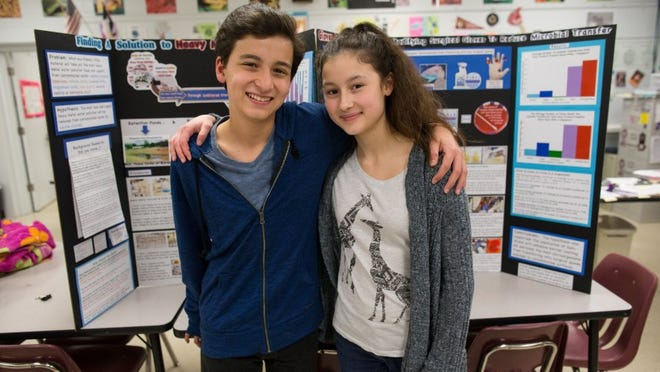 COURTNEY SACCO/CALLER-TIMES Nikolai and Tatiana Ortiz stand in front of their science fair projects regarding heavy metal water pollution Thursday, March 10, 2016.