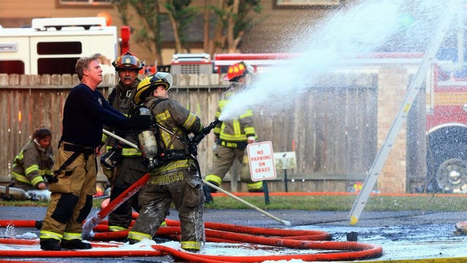Corpus Christi firefighters spray water to extinguish any hidden hot spots after a town house caught on fire Tuesday, May 10, 2016, at Lakewood Village in Corpus Christi. No major injuries were reported.
