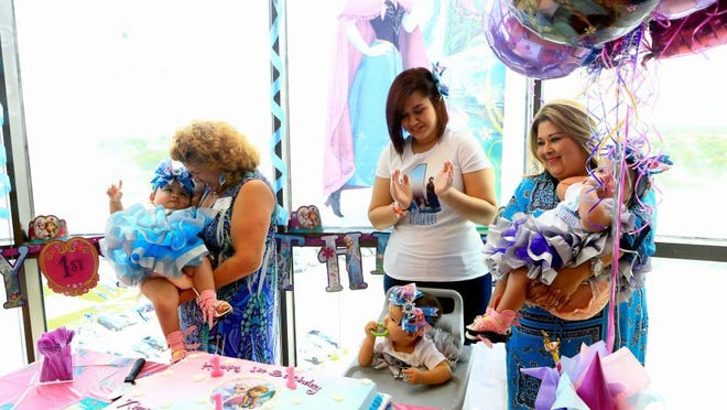 GABE HERNANDEZ/CALLER-TIMES Silvia Torres (center) sings Happy Birthday to her daughters Ximena, (left) Catalina (center) and Scarlett Hernandez -Torres (right). They triplets celebrated their first birthday with nurses and doctors Monday.