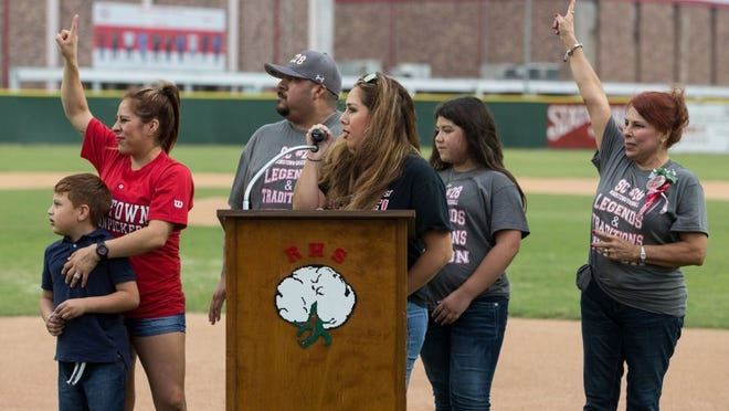 COURTNEY SACCO/CALLER-TIMES Steve Castro's family salutes the Robstown baseball team during the dedication ceremony for Steve Castro Field on Monday.