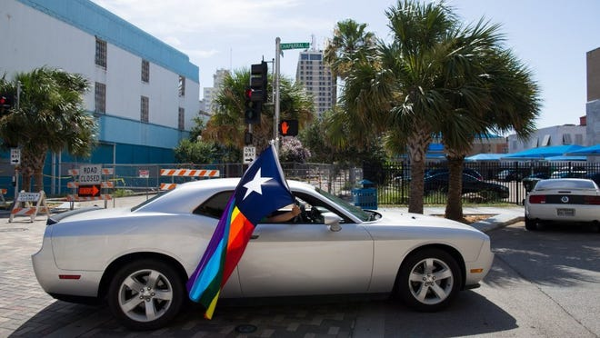 A passenger flies a rainbow Texas flag from a car window while traveling down North Chaparral Street during Corpus Christi's first Pride Downtown on Sunday, June 26, 2016.
