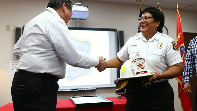 Battalion Chief Mickie Flores shakes hands with Chief Robert Rocha during her retirement party Thursday, Sept. 1, 2016, at the Corpus Christi Fire Department Headquarters.
