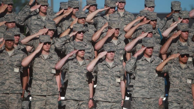 Service members salute during the opening at the Community College of the Air Force's commencement ceremony at the Goodfellow Air Force Base's parade grounds Wednesday, April 27, 2016. Michelle Gaitan/Standard-Times