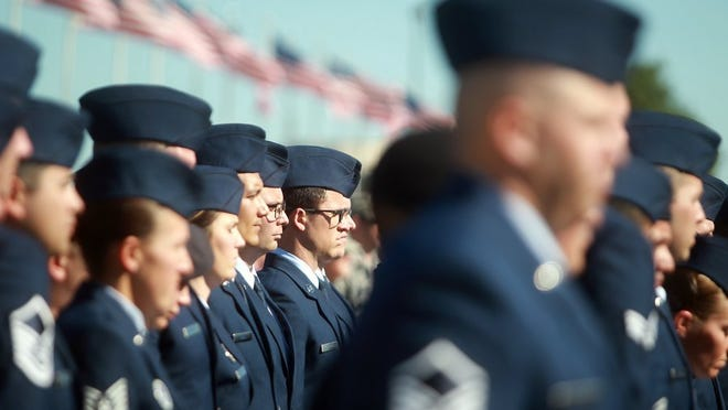 Graduates from the Community College of the Air Force stand in attention during their commencement ceremony at the Goodfellow Air Force Base.