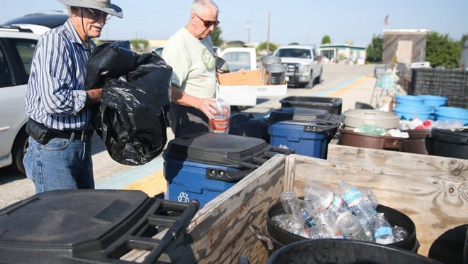 Yfat Yossifor / Standard-Times Robert Holtz (left) and Tim Hall empty recyclables at SAFE Recycling Center. Hall picks up recyclables at several locations to drop off at the center. Holtz is a member of VFW Post 1815 and volunteers to drop off recycling from the post.