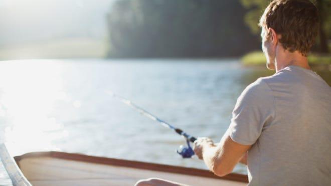 Man fishing in rowboat on calm lake