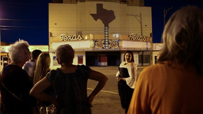 Caity Roberts tells ghost stories in front of the Texas Theatre during Be Theatre's Ghost Walk Saturday, Oct. 15, in downtown San Angelo.
