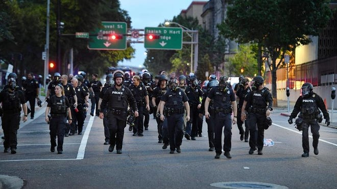 Police officers move down a Jacksonville street during a May 30 protest.